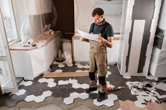 Focused diligent worker inspecting room and planning repairs work. repair of the dining room in the house, kitchen stock photography