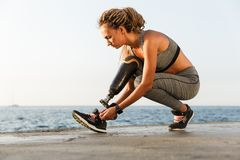 Focused disabled athlete woman with prosthetic leg. Tying shoelace outdoor stock photo