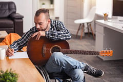 Focused disabled man engaged in songwriting. Final editing. Devoted handicapped young gentleman writing down new song lyrics and trying rhyming it while sitting Royalty Free Stock Image