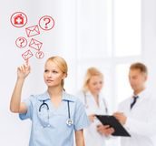 Focused doctor or nurse pointing to red envelope Royalty Free Stock Image