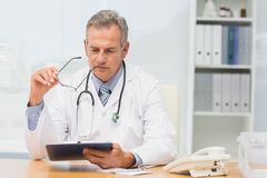 Focused doctor sitting at his desk with clipboard Stock Photo