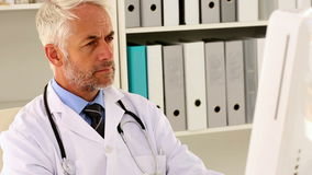 Focused doctor sitting at his desk using his computer stock footage