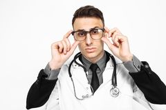 A focused doctor in a white robe and a stethoscope around his ne royalty free stock images