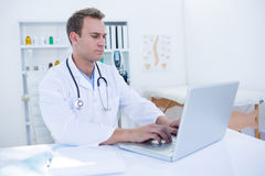 Focused doctor working with laptop Stock Photo