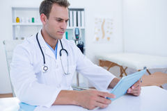 Focused doctor working with tablet computer Royalty Free Stock Photography