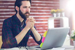 Focused editor with hand clasped using laptop. In creative office Stock Photography