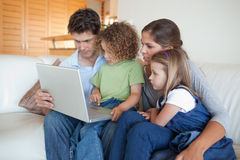 Focused family using a laptop Stock Photos