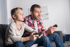 Father and son playing with joysticks. Focused father and son playing with joysticks and looking away at home Stock Photo