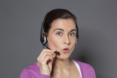 Focused female advisor answering a phone call on headset Royalty Free Stock Images