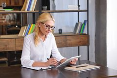 Focused female counselor in eyeglasses looking at digital tablet screen at table. In office royalty free stock photo