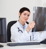 Focused female doctor holding a set of X-ray. While lookinigat the camera Stock Photo