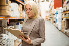 Focused female manager holding clipboard Stock Photography