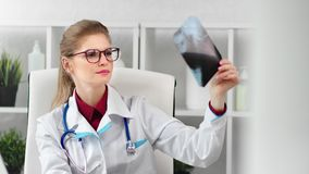 Focused female medical worker in glasses and uniform examining patient x-ray medium close-up