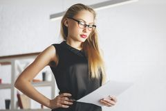 Focused female secretary portrait. Portrait of focused female secretary with glasses and document in hand. Blurry office background. Work, job, occupation Royalty Free Stock Photo