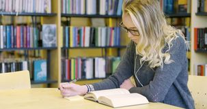 Focused female student reading books in school library stock video footage