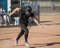 Focused on first base. Fast high school softball player sprinting stock image