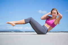 Focused fit blonde doing yoga on the beach Royalty Free Stock Images