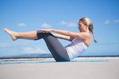 Focused fit blonde doing yoga on the beach Stock Images