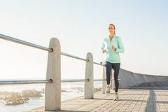 Focused fit blonde jogging at promenade Royalty Free Stock Image