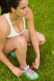 Focused fit brunette tying her shoelace Royalty Free Stock Photo