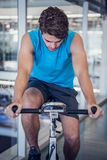 Focused fit man on the spin bike. At the gym Stock Photography