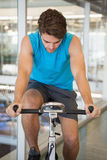 Focused fit man on the spin bike. At the gym Royalty Free Stock Images