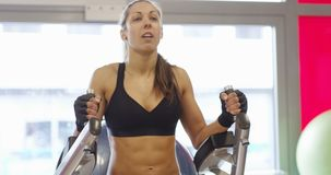 Focused fitness woman workout her abs in fitness gym stock video