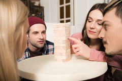 Focused friends playing jenga game together at home Royalty Free Stock Photo