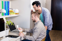 Focused gay couple looking at papers Royalty Free Stock Image