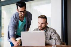 Focused gay couple using laptop Stock Photo