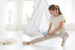 Focused girl doing warm up activities. Do not forget about your legs. Joyful schoolgirl wearing joggers stretching her legs and focusing on the exercise while Royalty Free Stock Photos