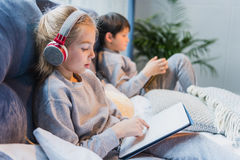 Focused girl in headphones and little boy using digital tablets. Side view of focused girl in headphones and little boy using digital tablets royalty free stock photography