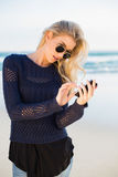 Focused gorgeous blonde text messaging. Focused gorgeous blonde on a beautiful wild beach text messaging Stock Photography