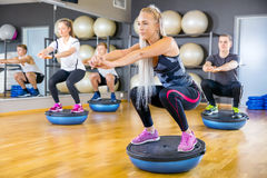 Focused group training squats on half ball at fitness gym. Dedicated people in workout team doing squats on half ball in a fitness gym class. Core muscle and Stock Image