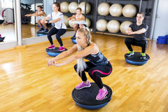 Focused group training squats on half ball at fitness gym Royalty Free Stock Photography