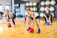 Focused group trains with kettlebells at fitness gym Royalty Free Stock Images