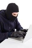 Focused hacker in balaclava hacking laptop Royalty Free Stock Photos