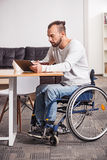 Focused handicapped man watching morning news Royalty Free Stock Image