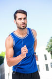 Focused handsome athlete jogging Stock Image