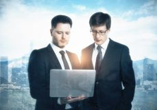 Teamwork and success concept. Focused handsome european businessmen using laptop together on bright city background. Teamwork and success concept. Double Royalty Free Stock Photos