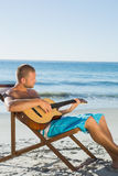Focused handsome man strumming guitar Stock Images