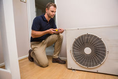 Focused handyman fixing air conditioning Stock Image
