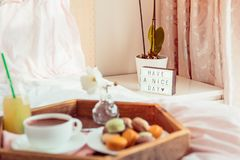 Focused Have a nice day text on lighted box on the bedside table and blurred wooden tray with coffee and macaroons breakfast on royalty free stock image