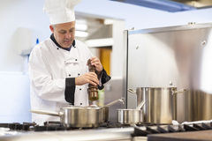 Focused head chef flavoring food with pepper Royalty Free Stock Photos