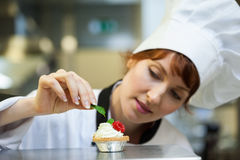 Focused head chef putting mint leaf on little cake Royalty Free Stock Image