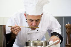 Focused head chef tasting sauce with wooden spoon Royalty Free Stock Photo