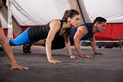 Focused on her push ups. Beautiful young brunette doing some push ups with some other people at a gym Royalty Free Stock Images