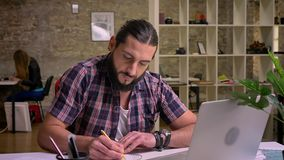 Focused on his writing caucasian guy is sitting cna precisely looking at his notes while sitting at desktop, work. Illustration, casual style stock video