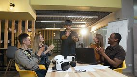 Focused japanese man using virtual reality glasses while his cowokers applauding him. Focused japanese man using virtual reality glasses while his cowokers stock footage