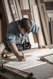 Focused joiner working in carpentry. Photo of focused joiner working in carpentry Stock Images